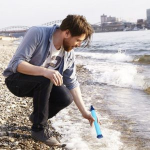 Man about to drink from a river using a filter straw survival tool